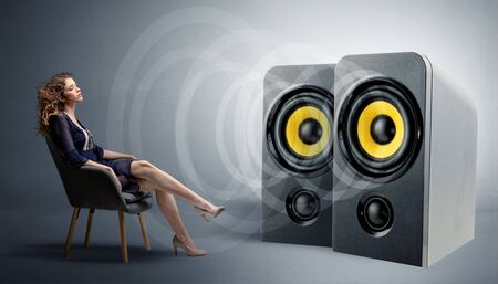 Stylish young lady sitting in a sofa and listening to big loudspeakers