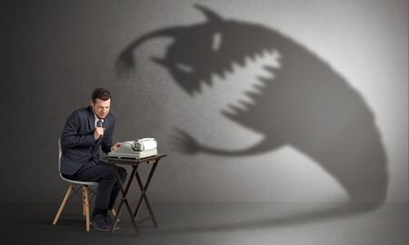 Little hard worker afraid of scary monster shadow Stock Photo