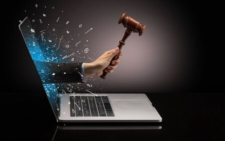 Hand with hammer coming out of a laptop with sparkling effects Stock Photo