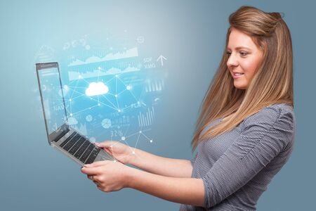 Woman holding laptop projecting cloud based system symbols and informations Stok Fotoğraf