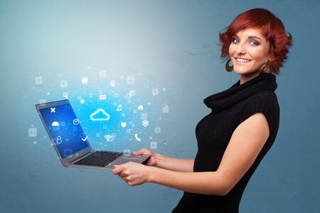 Woman holding laptop projecting notifications, symbols and information based on cloud technology system