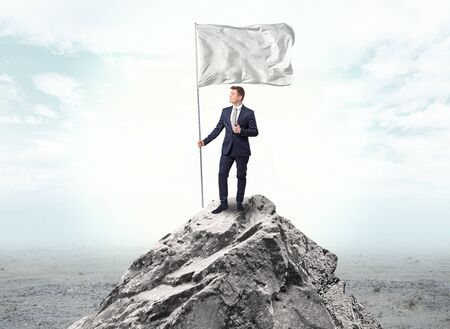 Handsome businessman on the top of the mountain with white flag Standard-Bild