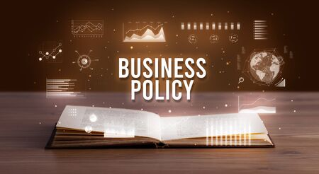 BUSINESS POLICY inscription coming out from an open book, creative business concept Stock Photo
