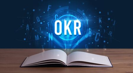 OKR inscription coming out from an open book, digital technology concept