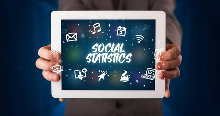 Young business person working on tablet and shows the inscription: SOCIAL STATISTICS Stockfoto