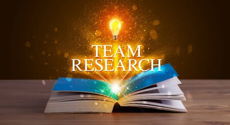 TEAM RESEARCH inscription coming out from an open book, educational concept Stockfoto