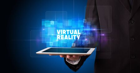 Young business person working on tablet and shows the inscription: VIRTUAL REALITY
