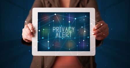 Young business person working on tablet and shows the digital sign: PRIVACY ALERT Stockfoto