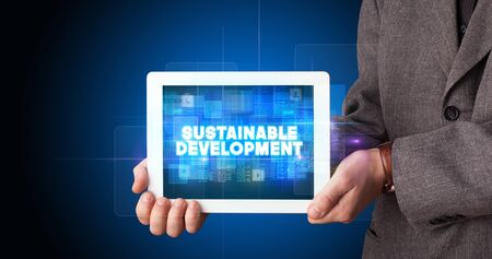 Young business person working on tablet and shows the inscription: SUSTAINABLE DEVELOPMENT Stock fotó
