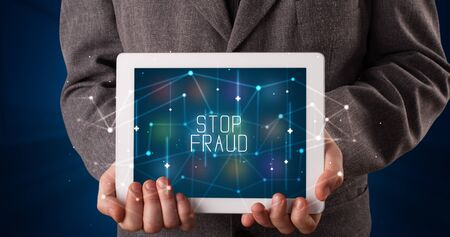 Young business person working on tablet and shows the digital sign: STOP FRAUD