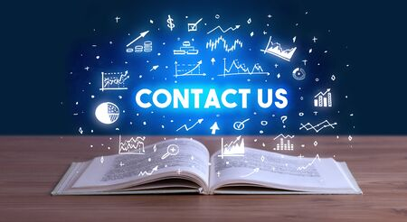 CONTACT US inscription coming out from an open book, business concept Stock Photo