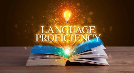 LANGUAGE PROFICIENCY inscription coming out from an open book, educational concept Stock Photo