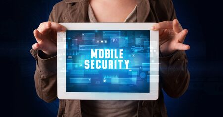 Young business person working on tablet and shows the digital sign: MOBILE SECURITY Stock Photo