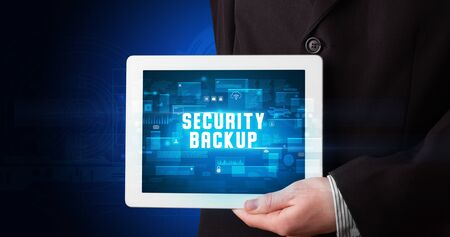 Young business person working on tablet and shows the digital sign: SECURITY BACKUP Stock Photo