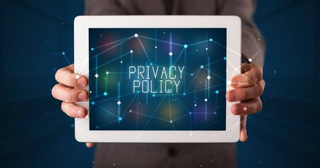 Young business person working on tablet and shows the digital sign: PRIVACY POLICY