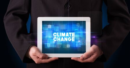 Young business person working on tablet and shows the inscription: CLIMATE CHANGE