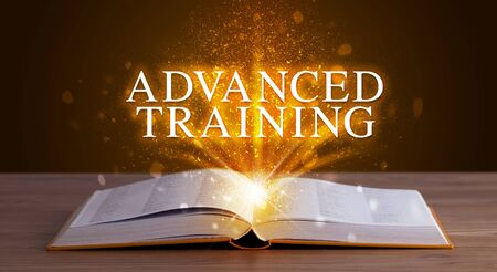 ADVANCED TRAINING inscription coming out from an open book, educational concept Stock Photo