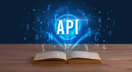 API inscription coming out from an open book, digital technology concept Stock Photo