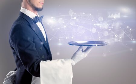Young waiter serving financial concept on a metal tray Stock Photo