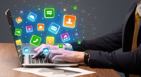 Businessman hand typing on laptop with flying application icons around