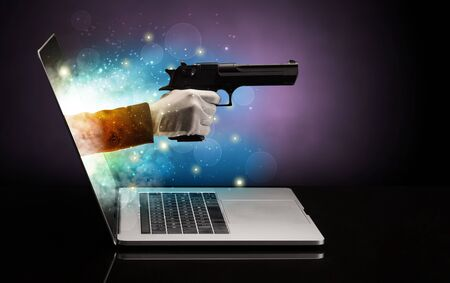 Hand with gun coming out of a laptop with sparkling effects 免版税图像