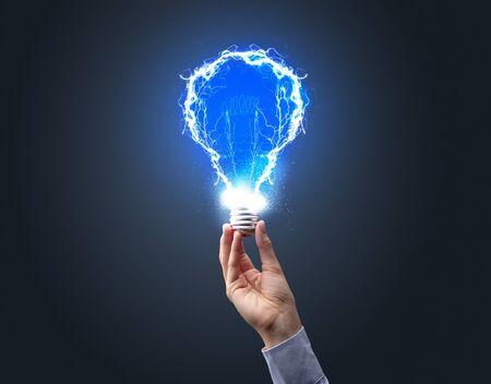 Hand holding shiny light bulb on dark background. New idea concept