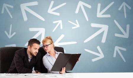 Geschäftsperson, die am Schreibtisch mit unterschiedlichem Richtungskonzept sitzt Standard-Bild