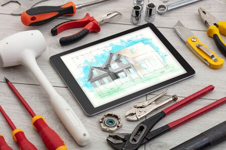 Tablet with construction tools and house plan concept 写真素材
