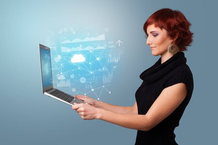 Woman holding laptop projecting cloud based system symbols and informations Banque d'images - 130070024