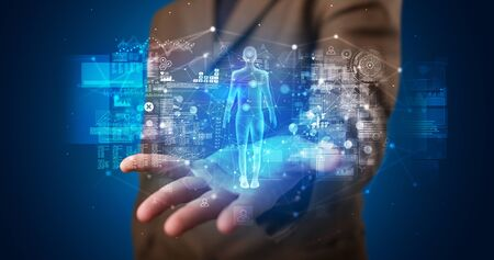 Young person holding hologram projection displaying health related graphs and symbols Banque d'images - 130069846