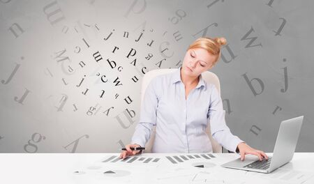 Business person sitting at desk with editorial and letters concept