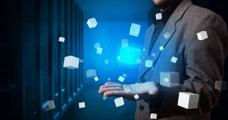 Person holding hologram projection displaying white cubes in server room Banque d'images - 130068424