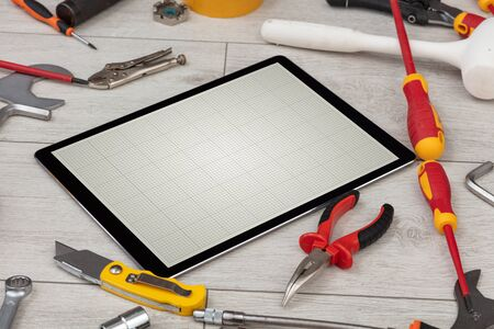 Household tools and tablet with grid screen concept 写真素材