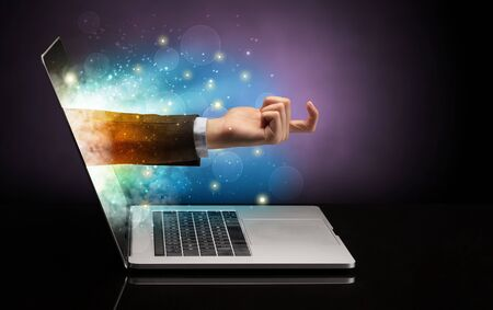 Hand coming out of a laptop with sparkling effects