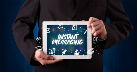 Young business person working on tablet and shows the inscription: INSTANT MESSAGING
