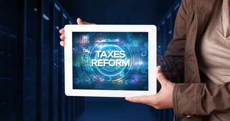 Young business person working on tablet and shows the inscription: TAXES REFORM, business concept