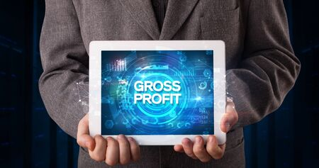 Young business person working on tablet and shows the inscription: GROSS PROFIT, business concept