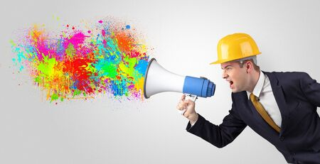 Young architect constructor yelling with megaphone with and colorful splash concept Фото со стока