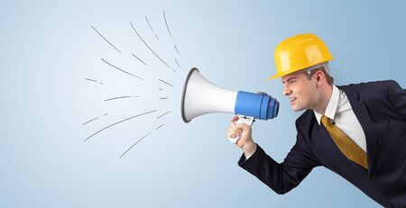 Young architect constructor yelling with megaphone and copyspace