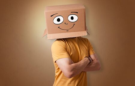 Young boy standing and gesturing with a cardboard box on his head 스톡 콘텐츠