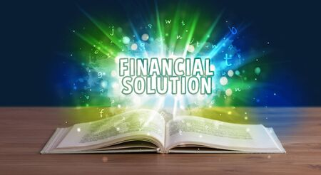 FINANCIAL SOLUTION inscription coming out from an open book, educational concept Stok Fotoğraf