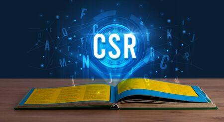 CSR inscription coming out from an open book, digital technology concept Reklamní fotografie