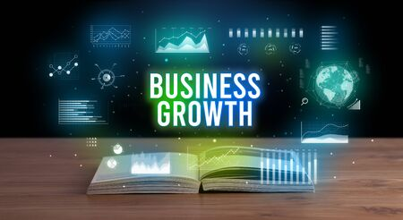 BUSINESS GROWTH inscription coming out from an open book, creative business concept