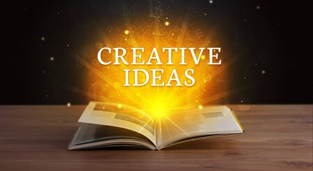 CREATIVE IDEAS inscription coming out from an open book, educational concept Stok Fotoğraf