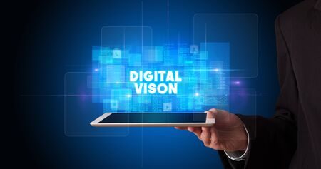 Young business person working on tablet and shows the inscription: DIGITAL VISON
