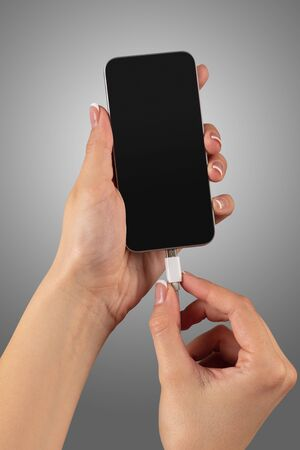 Close-up view of hand charging smartphone