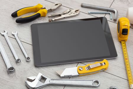 Tablet with empty screen and construction tools around Reklamní fotografie