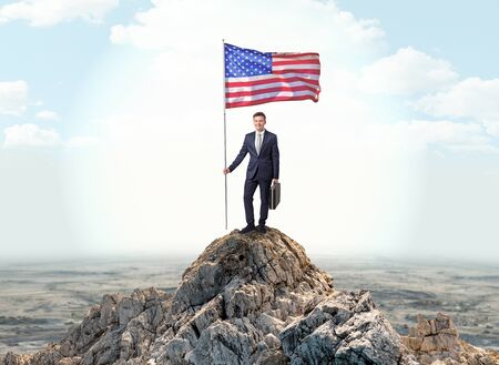 Successful businessman on the top of a mountain holding victory flag