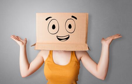 Young woman standing and gesturing with a cardboard box on her head with drawn smiley face
