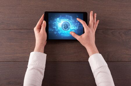 Hand working on tablet with cryptocurrency and network concept